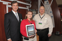 Lisa Fisher (middle) of B&R Camper Sales in Theodore, Ala., was the winner of the iPad giveaway on Wednesday. Presenting the iPad was Doug Whyte, president of Dometic USA (right) and Brad Sargent, Dometic vice president of marketing (left).