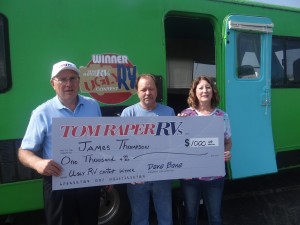 "Tom Raper RVs GM Ed Unger presents a check for $1,000 to the""Ugly RV"" contest winner James Thompson III and his friend Vickie Caskey in front of ""The Pickle"""